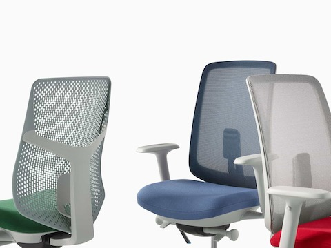 A close-up view of a Verus Chair with a green Triflex back, a Verus Chair with a blue seat and suspension back, and a Verus Chair with a grey suspension back with a red seat.