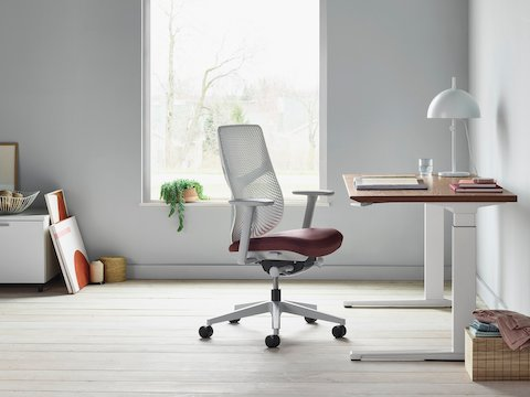 A Verus Chair with a dark red upholstered seat and white Triflex back next to a Renew Sit-to-Stand Table in a home office with gray walls and light hardwood floors.