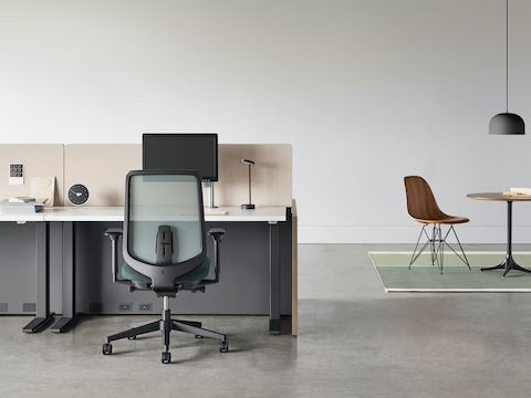A black Verus chair with a black Motia Sit-to-Stand Table and Canvas Channel workstation with a Nelson Pedestal Table and Eames Moulded Wood Side Chair in the background.