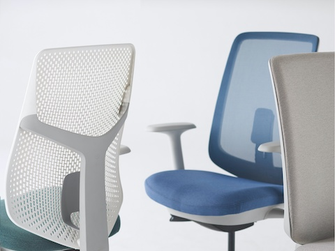 A close-up view of a Verus Chair with a green Triflex back, a Verus Chair with a blue upholstered seat and blue suspension back, and a Verus Chair with a grey upholstered back.