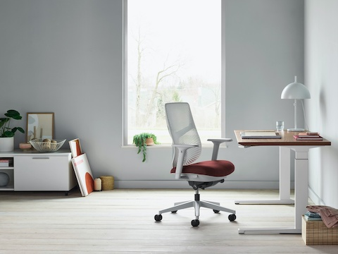 A Verus Chair with a dark red upholstered seat and white Triflex back next to a Renew Sit-to-Stand Table in a home office with grey walls and light hardwood floors.
