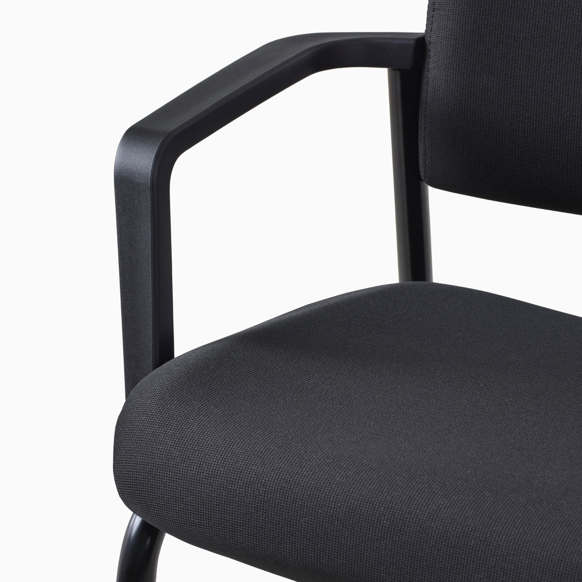 A close-up view of a Verus Side Chair's black upholstered seat with arms.