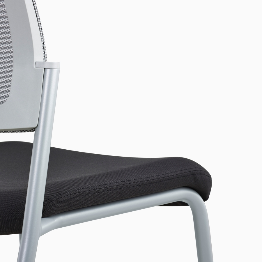 A close-up view of a gray Verus Side Chair's black upholstered seat with no arms.
