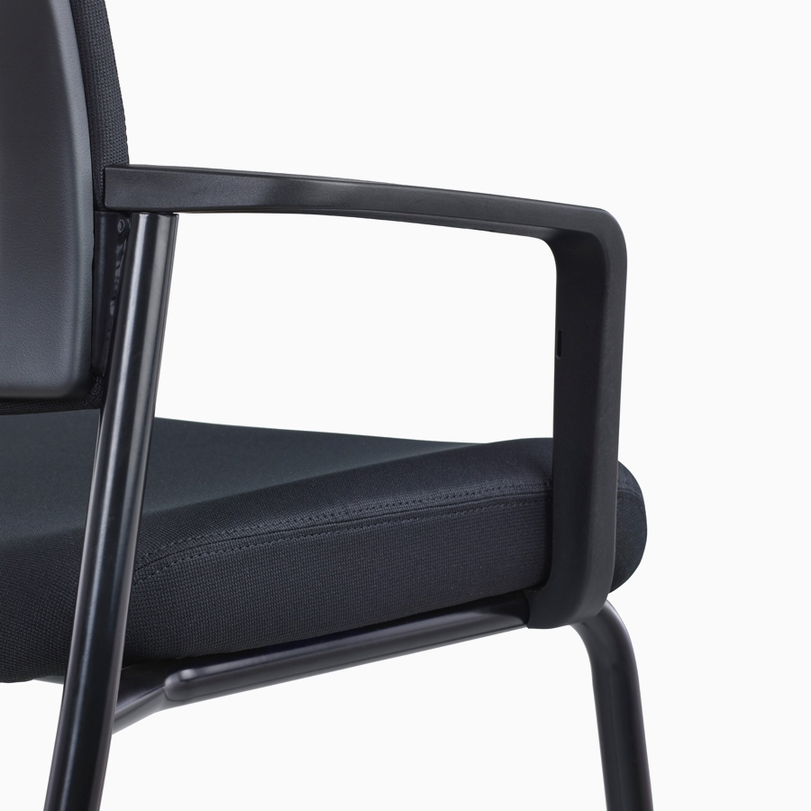 A close-up view of a dark blue Verus Side Chair's upholstered seat with fixed arms.