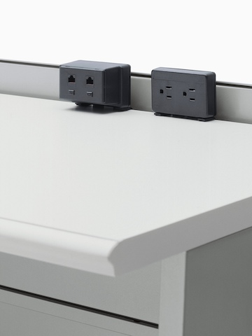 A Connect Voice/Data Outlet and a Connect two-outlet Electrical Distributor, both attached to the back of a work surface.