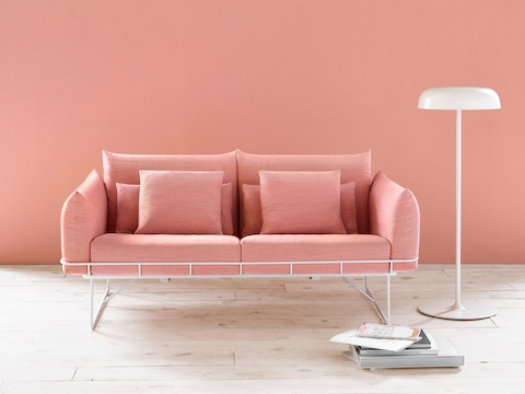Two-cushion Wireframe Sofa in salmon with white frame, viewed from the front next to a floor lamp.