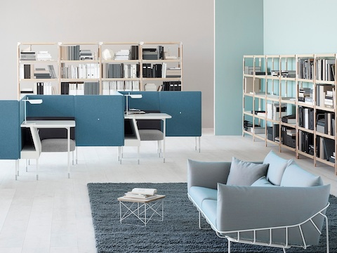 Light blue Wireframe Sofa with white frame, in a lounge space near two Public Office Landscape workstations with task lighting.