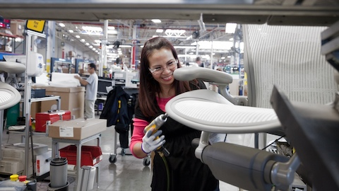 A Herman Miller Group employee smiles as she attaches parts to a light gray Aeron Chair on an assembly line.