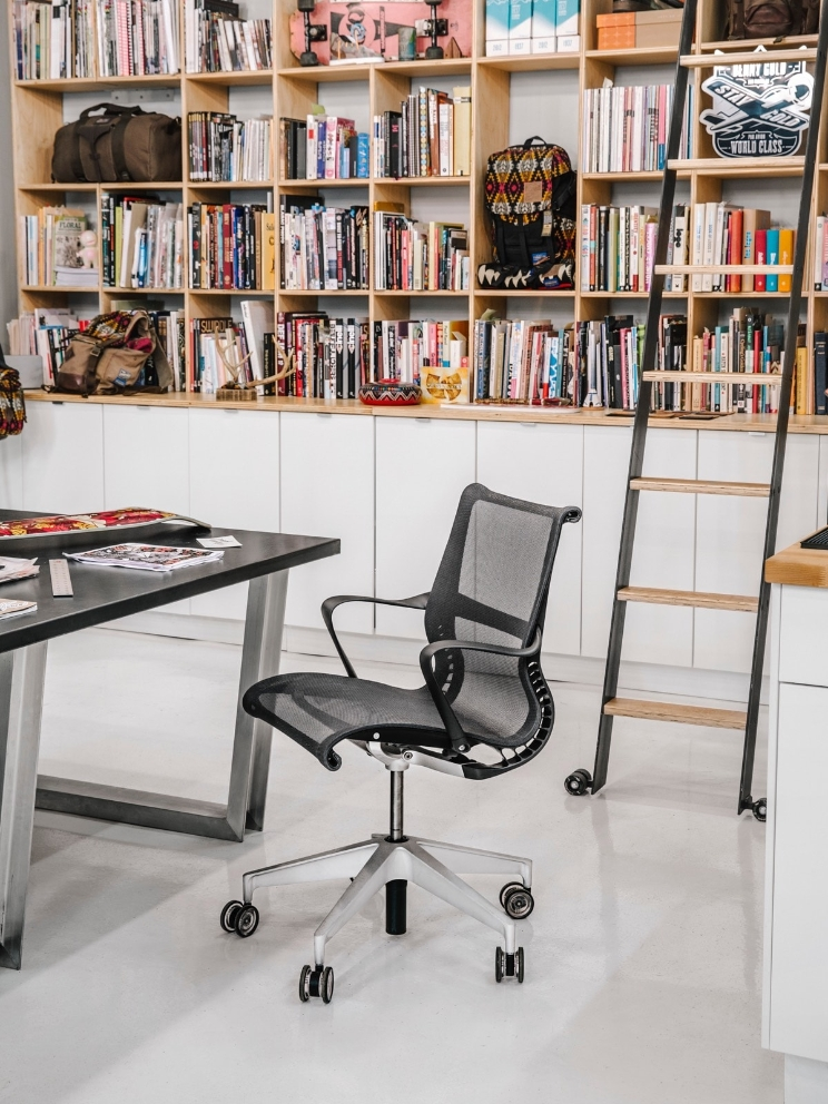 A Setu chair sits empty by a desk, with a large bookcase and ladder in the background.
