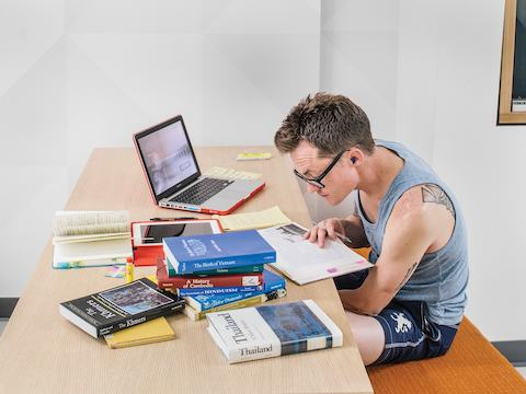 A student studies among a stack of books and a laptop.