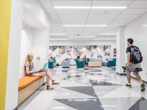University students study admist bench and lounge seating within a corridor.