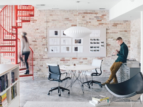 An open workspace with a red spiral staircase and pendant light.