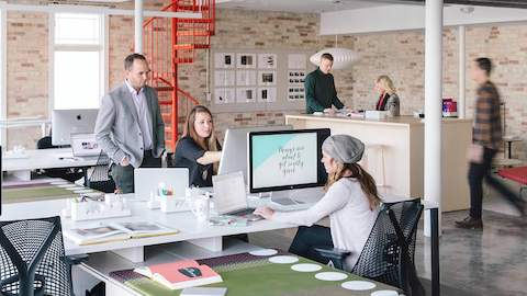 People work and converse inside of an open office space with several Sayl chairs.