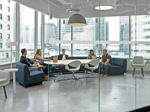 Five people sit on blue Chadwick Modular Seating in a glass-walled conference room. Two white Nelson Swag Leg chairs sit across the table from them, and a gray Saiba Chair sits off to the side.