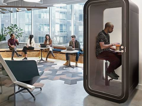 A person sits on a stool in a Framery O Office Phone Booth. Nearby, four people sit, chat, and work on laptops in a window seat.