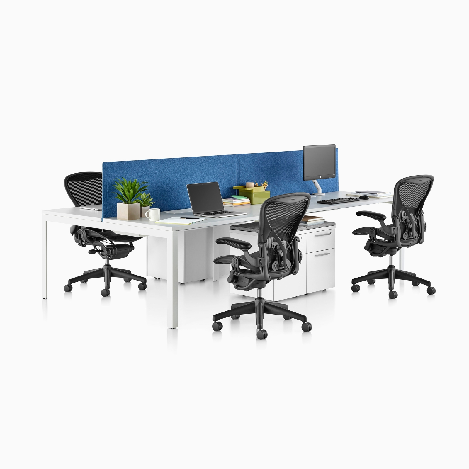 A side view of white Layout Studio desks seperated by a blue divider scrren and three black Aeron Chairs. Select to go to the Layout Studio product page.