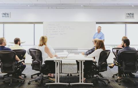 Employees sit in Aeron chairs and listen to a presentation inside of a meeting room.