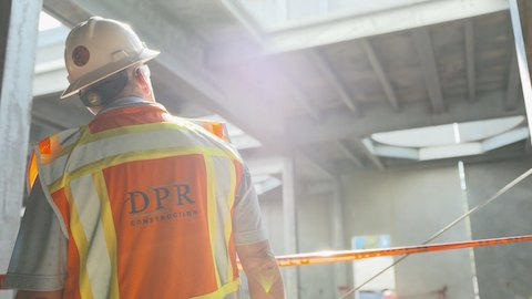 A man, viewed from behind, wears a hard hat and an orange safety vest bearing the words DPR Construction.