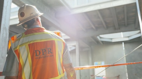 A man, viewed from behind, wears a hard hat and orange safety vest. Select to go to a case study featuring DPR Construction.