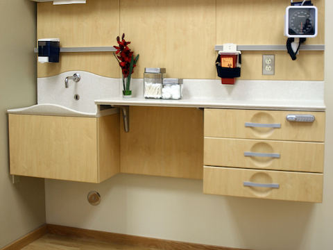 A clinic setup showing a splashless sink, cantilevering, and various cabinets.