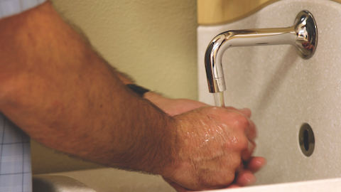 A physician washes his hands at a sink inside of a medical area.
