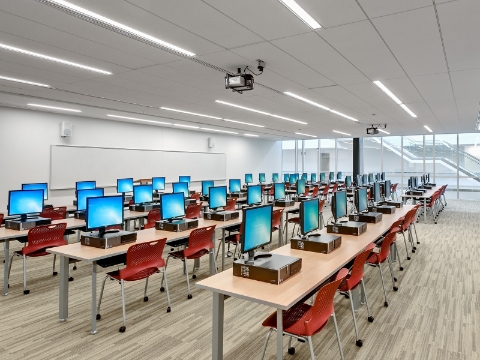 Computers sit atop several rows of desk and chairs within a university building.