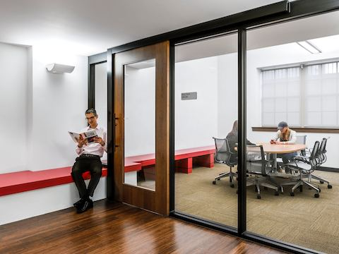 A man reads a textbook while waiting outside of a glass-walled meeting room.