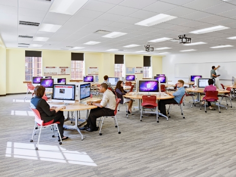 Students sit at round computer tables inside of a university classroom.