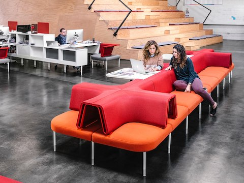 People work and discuss projects while seated at a desk and lounge sofas.
