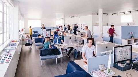 Young workers in an open office. Select to read a case study about the Public Office Landscape system at fuseproject.