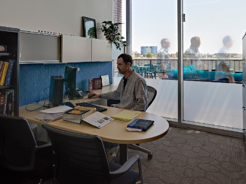 A faculty member works at his computer inside of his office area.