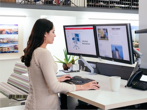 Woman standing at a sit-to-stand desk, looking at two computer monitors.