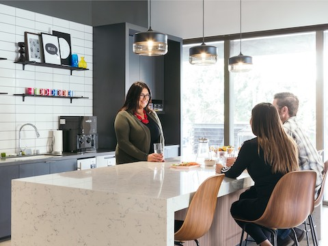 A man and a woman sitting at a counter socializing with a woman across from them in a kitchen.