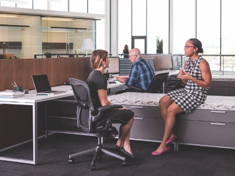 Employees work and converse while seated in an open office environment.