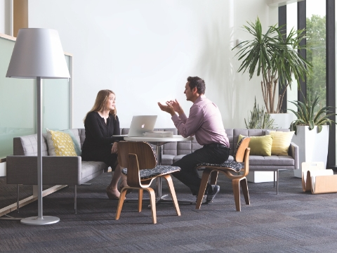 Two people sit and talk in an office lounge area.