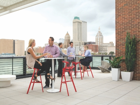 People talk outside on a patio overlooking a downtown area.