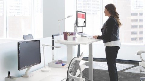 A woman types on a laptop at a standing desk near a window.