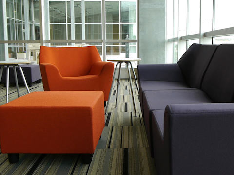 A lounge area setup with navy blue and burnt orange Swoop seating.