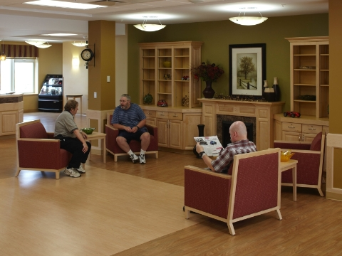 Residents and staff of an assisted living center mingle in a lounge area.