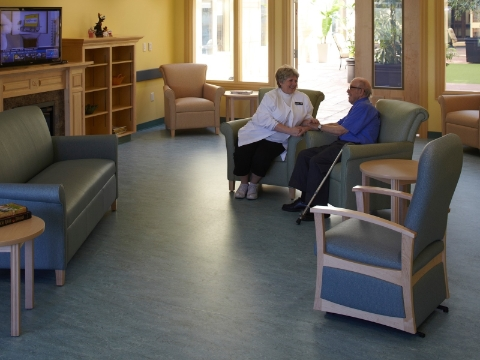 A staff member visits with a resident of an assisted living center inside a T.V. room.
