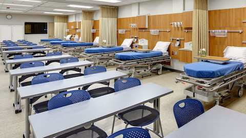 A healthcare classroom combines chairs and desks with mock patient rooms.