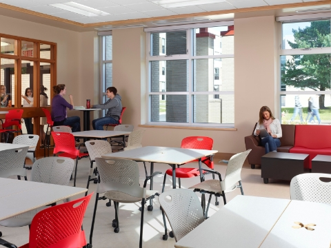 Students sit amidst Cper chairs and Swoop lounge seating inside of an open common area.