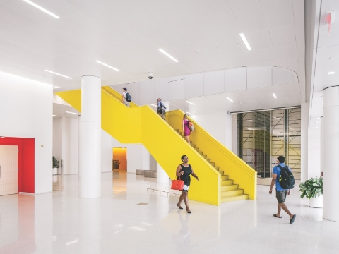People inside of a library lobby, with a bold yellow staircase at the center.
