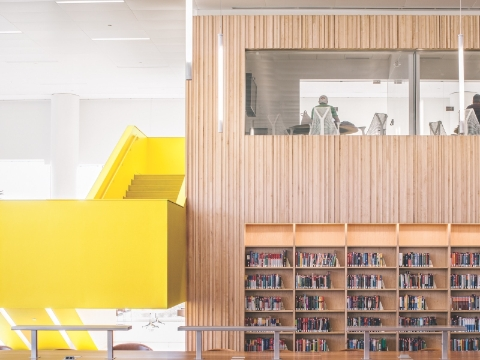 Shelves of library books sit behind benches.