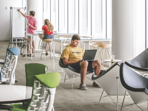 Students studying in an open lounge space within a library.
