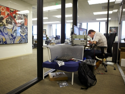 A man focuses on his work while inside of a glass-walled office space.