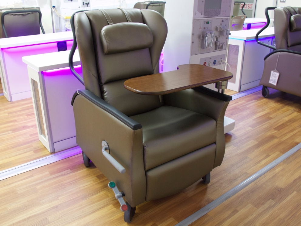 A brown Nemschoff Serenity Chair sits inside of a mobile dialysis unit.