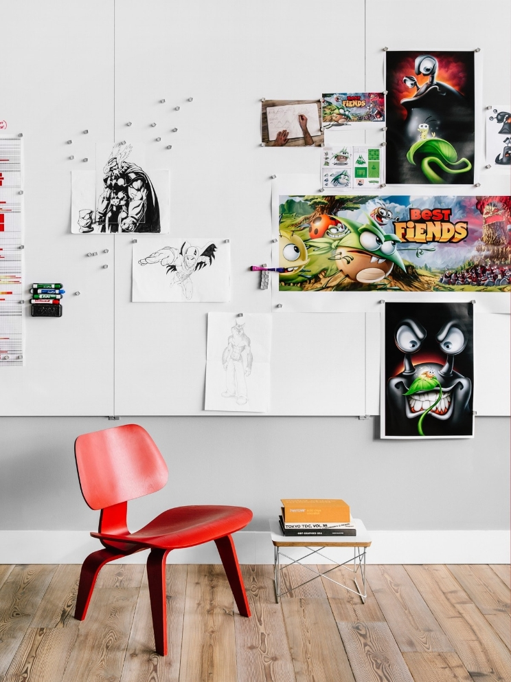 An office wall full of sketches and various illustrations behind a wood chair.