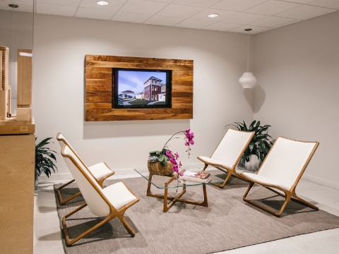 An inviting office lobby features Geiger Scissor chairs and a glass coffee table.