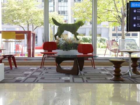 An office lobby displays Eames chairs and stools placed near windows.